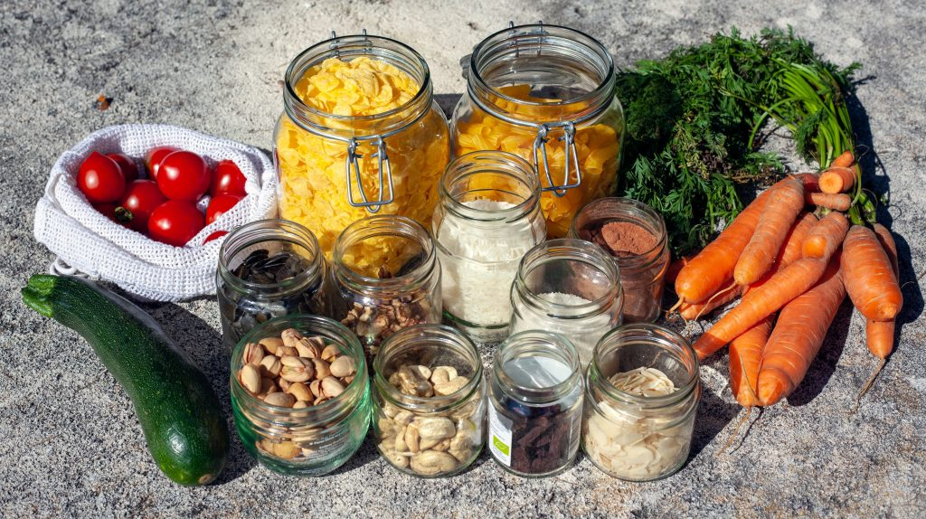 A selection of foods in reusable containers and loose vegetables - one way to reduce food waste.
